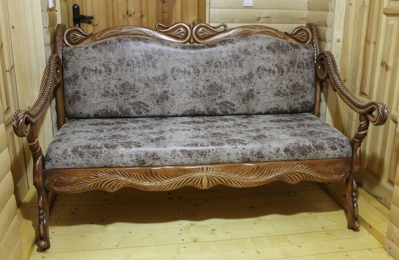 Leather sofa with carved wood trim will be a real finding for your living room.