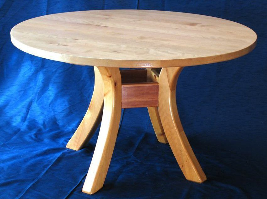 The small round wood kitchen table with rough wood and metal holders will beautify any interior.