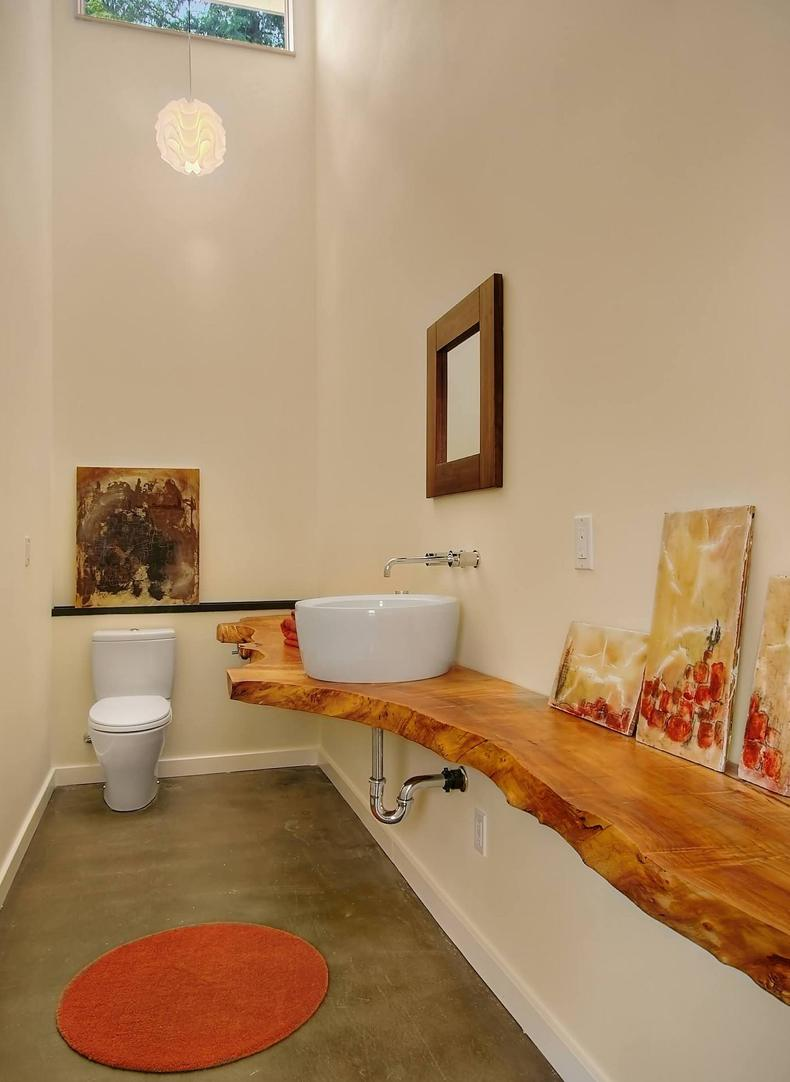 Rustic log vanity gives shiny and reflective look to the bathroom.